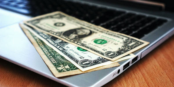 Bank notes on laptop NetSuite Salary Survey